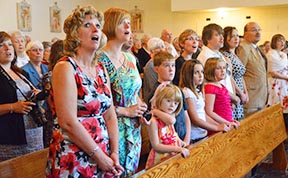 Celebrating parishioners raise their voices in praise at Our Lady of the Assumption's 100th anniversary Mass.