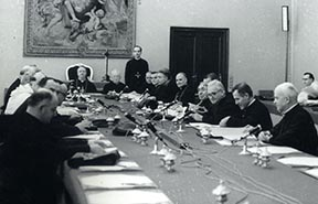Cardinal Alfredo Ottaviani sits at the far end of the table chairing a meeting of the Theological Commission, which prepared several documents for consideration at Vatican II.