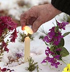 A woman lights a candle on a grave at a cemetery in the village of Ivenets, Belarus, Nov. 1. Catholics in Belarus marked All Saints' Day by visiting the graves of their relatives and friends.