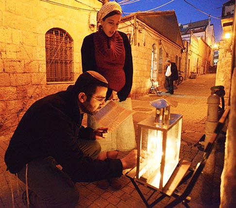 An Ultra-Orthodox Jewish couple lights candles on the third night of the Jewish holiday of Hanukkah, The Festival of Lights in Jerusalem Dec. 10. In Israel, families gather each evening during the eight-day celebration to light a candle on the menorah, eat traditional foods and exchange gifts.