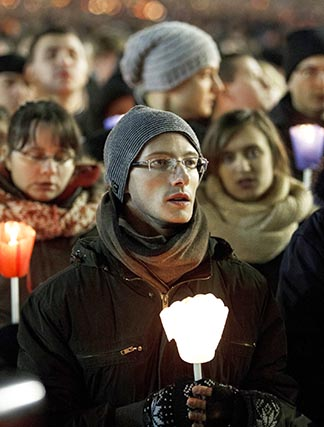 Young people hold candles as they participate in a Taize prayer service with Pope Benedict in St. Peter's Square at the Vatican Dec. 29.