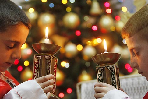 Two Iraqi boys hold candles as they pray for peace in Iraq and Syria during a Mass in Amman, Jordan, Dec. 23.