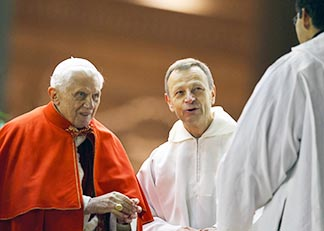 Pope Benedict greets members of the Taize ecumenical community as Brother Alois Leser, prior of the community, looks on during a prayer service in St. Peter's Square Dec. 29.