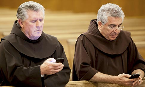 Franciscan Brothers Richard Mcfeely and Robert Frazzetta read prayer requests on their mobile phones Jan. 3 at St. Anthony Friary in Butler, N.J. The largest group of Franciscan friars in the United States is offering the faithful a new way to pray in the digital age by accepting prayer requests via text messages.