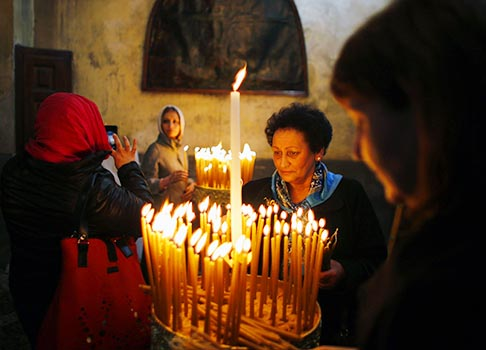 Worshippers stand near candles in the Church of the Nativity in Bethlehem, West Bank, Jan. 18. In the grotto of the church, a silver star marks the site of Christ's birth.