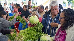 Local residents peruse vegetables for sale outside the chapel at the Home of Divine Providence in Santa Tecla, El Salvador.