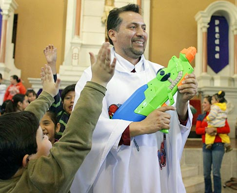Fr. Humberto Alvarez sprays holy water from a water gun to bless the children during Mass at a church in Saltillo, Mexico, Feb. 17. Alvarez wears robes with cartoon characters and uses a water gun to bless the congregation when conducting children's Mass, but slips back into his regular robes when celebrating Mass for adults.