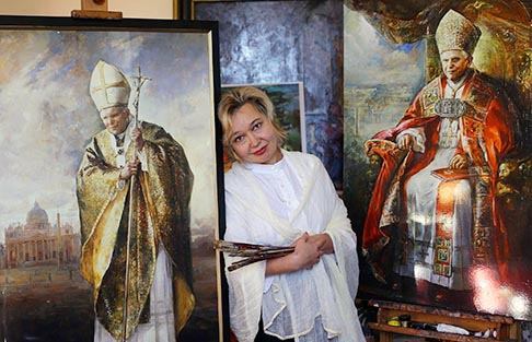 Russian painter Natalia Tsarkova poses next to a copy of a portrait of Pope Benedict XVI and another of Blessed John Paul II in her studio in downtown Rome Feb. 14. Tsarkova painted the official portrait of Pope Benedict in 2007 and the official portrait of Blessed John Paul for the 2000 Jubilee.