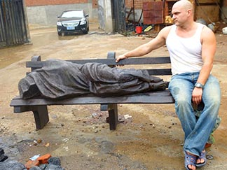 Timothy Schmalz sits on a bench with his Homeless Jesus.