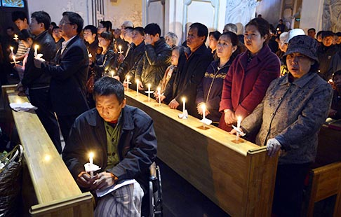Worshippers hold candles during the Easter Vigil at a Catholic church in Taiyuan, China, March 30.