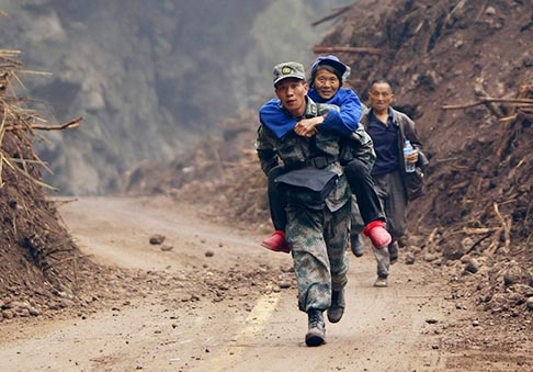 A soldier carries a survivor as he runs on a stretch of the road April 22, two days after an earthquake hit Sichuan province, China. Thousands of soldiers and rescuers responded to magnitude 6.6 earthquake that struck April 20, killing at least 186 people and injuring more than 11,000.
