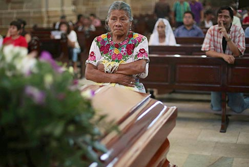 A woman prays at the casket of Auxiliary Bishop Juan Gerardi Conedera in observance of the 15th anniversary of his murder before it is moved to a new crypt at the cathedral in Guatemala City April 25. Gerardi was murdered April 26, 1998, two days after releasing a report blaming the Guatemalan military for a majority of the 200,000 deaths and human rights violations that occurred during Guatemala's 36-year civil war.