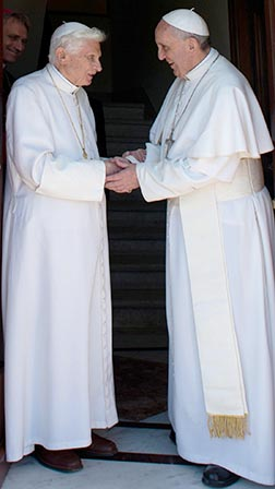 Retired Pope Benedict XVI greets Pope Francis at the Vatican May 2