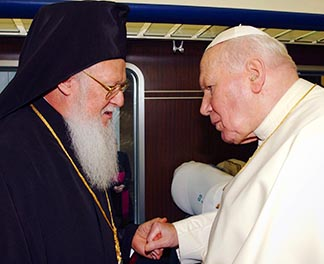 Pope John Paul II greets Ecumenical Orthodox Patriarch Bartholomew in 2002. The pope and patriarch were both champions of full unity between Eastern and Western churches.