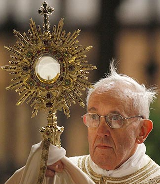 Pope Francis holds the Blessed Sacrament in a monstrance during the observance of the feast of Corpus Christi in Rome May 30.