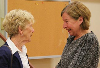 Judy Graves (right) greets a close friend after her retirement party.