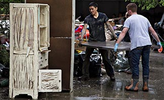 People pitch in to help remove soaked furniture from their homes in one of the flooded areas in Calgary.