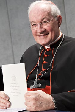 Cardinal Marc Ouellet, perfect of the Congregation for Bishops, holds a copy of Pope Francis' encyclical Lumen Fidei (The Light of Faith) during a news conference at the Vatican July 5.
