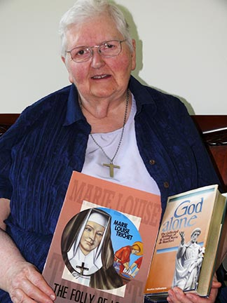 Sr. Harriet Hermary, a former teacher at Theresetta School, holds two books related to the founding of the Daughters of Wisdom.