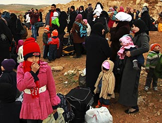 Syrian refugees rest after they crossed into Jordan with their families from Syria.