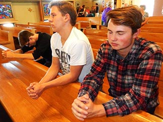 Teens Gregoire Mokuin, Josh Marple and Gabriel Clark celebrate their faith at Assumption Parish.