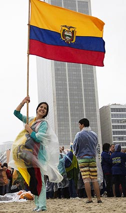A pilgrim from Ecuador holds her country's flag on Copacabana beach in Rio de Janeiro.