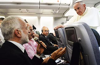 Pope Francis listens to a question from a journalist on his flight heading back to Rome July 28.