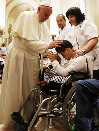 Pope Francis blesses a disabled person during his visit at the Serafico Institute in Assisi, Italy.