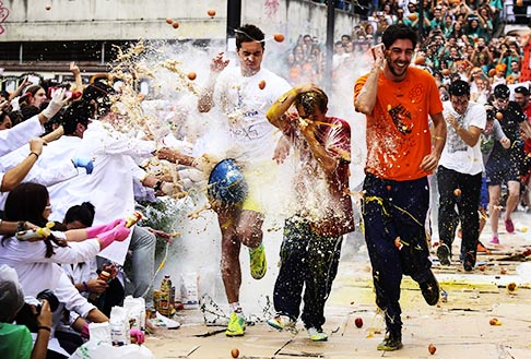 First-year medical students run while seniors spray them with different types of sauces, liquids, flour and eggs as part of an annual tradition during a celebration in honour of St. Luke, patron saint of doctors, at Granada University in Spain Oct. 17.