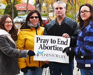 Keeping vigil with rosaries and pro-life banners, across the street from Woman's Health Options, were Maryanne Testa, Clair Connell, Ernie Paquette and Megan Testa.