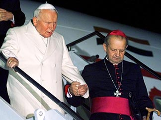 Then-Bishop Stanislaw Dziwisz helps Pope John Paul II down the stairs of an airplane arriving in Rome after a trip to India and Georgia in 1999.