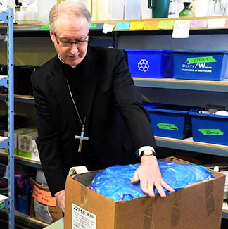 Archbishop Richard Smith finishes packing a hamper for a needy family.