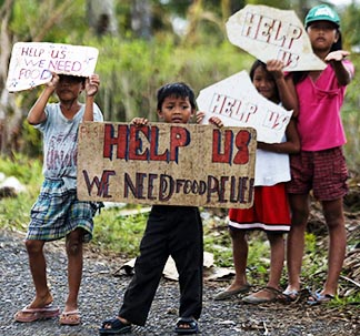 Children in the Philippines stand along a road with signs urging passing aid trucks to stop.