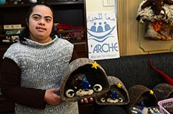 Ayat Sand, 21, a Palestinian member of L'Arche, holds a Nativity set made from felted wool, from Bethlehem sheep at the Ma'an lil-Hayat.