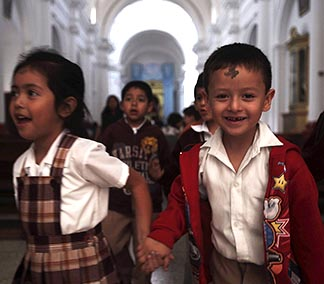 Children leave a church after receiving ashes during Ash Wednesday Mass in Guatemala City last year.