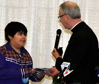 Joreal Orr, a student at Ben Calf Robe-St. Clare School in Edmonton and Archbishop Richard Smith exchanged gifts following Smith's apology for Catholic involvement in residential schools.