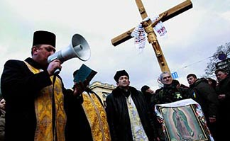 An Orthodox clergyman leads a prayer service alongside a crucifix and an image of Our Lady of Guadalupe Feb. 24 at the site in Kyiv where people have been killed in recent clashes protesting against the government.