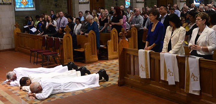 Deacons Roger Reilander, Gem Mella and Hyland Fraser lie prostrate before the altar prior to their ordination to the permanent diaconate May 31 at St. Joseph's Basilica as their wives Joyce Reilander, Dada Mella and Harriet Fraser (right) look on.