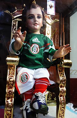 A Holy Child of Miracles statue in a church in Mexico City is dressed in the national team uniform for the World Cup.
