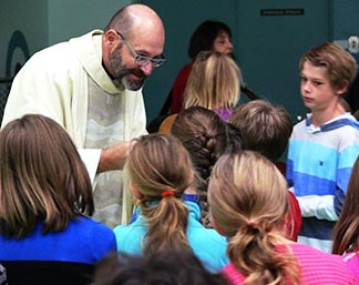 Fr. Leo Hofmann distributes Communion to children during a teaching Mass at St. Benedict's School in Leduc, one of several ways parishes in the Edmonton Archdiocese try to involve children more in the liturgy.