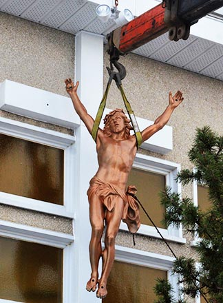 The restored statue of Jesus is lifted back into place on the cross on the west side of St. Agnes Church.