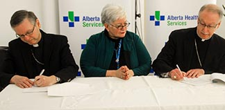 Bishop David Motiuk, Vickie Kaminski, president and CEO of Alberta Health Services, and Archbishop Richard Smith sign an access agreement that clarifies the roles and responsibilities of appointed Catholic clergy in Alberta Health Services facilities across the province.