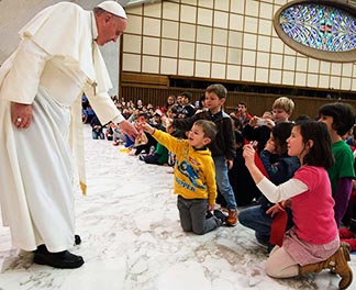 Pope Francis hands gifts to children during a meeting with an Italian association for large families to mark the feast of the Holy Family in Paul VI hall at the Vatican Dec. 28