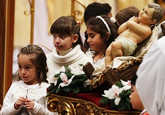 Children gather near a figurine of the baby Jesus at the conclusion of Pope Francis' celebration of Christmas Eve Mass in St. Peter's Basilica at the Vatican Dec. 24.