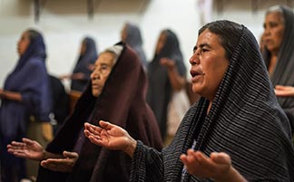 Women pray during Mass in the Mexican state of Oaxaca. Researchers are finding that daily meditation can heighten one's sense of peace and compassion.
