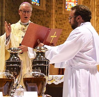 Archbishop Richard Smith, aided by seminarian Roger Niedzielski, blesses the holy oils at the annual Chrism Mass March 30 at St. Joseph's Basilica in Edmonton.