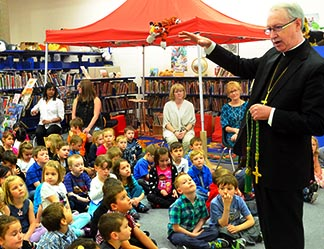 Archbishop Richard Smith explains the significance of a green cord which holds his cross during an April 13 visit with kindergarten and Grade 1 students at J. J. Nearing School in St. Albert.