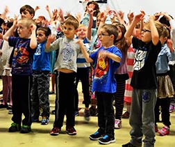 Students at St. Albert's J. J. Nearing School welcome Archbishop Smith April 13 at an assembly in the school gym.