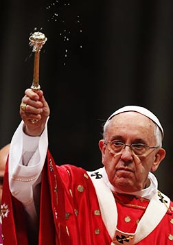 Pope Francis blesses the faithful with holy water as he celebrates Pentecost Mass May 24.
