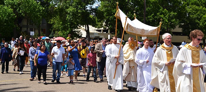 Hundreds of people followed Archbishop Richard Smith carrying the Blessed Sacrament through the streets east of St. Joseph Basilica during Corpus Christi procession June 7.